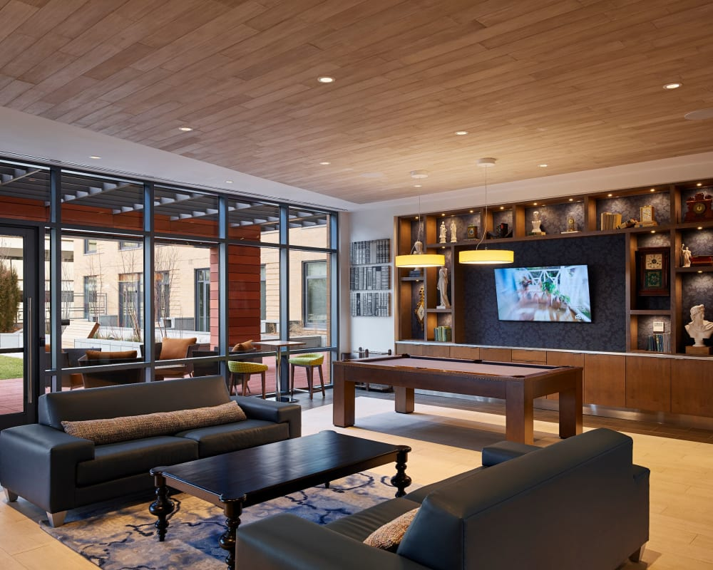Rustic clubhouse with bar seating, flat-screen TVs and a fireplace at Solaire 8250 Georgia in Silver Spring, Maryland