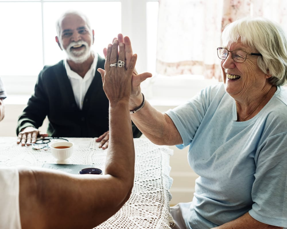 Residents high fiving while sitting across each other at a table in Keepsake Village at Greenpoint in Liverpool, New York