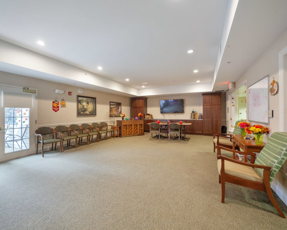 Group activity room with chairs along the walls and a tv at The Hearth at Stones Crossing in Greenwood, Indiana