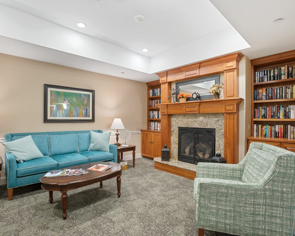 Fireplace lounge with bookshelves and seating at The Hearth at Hendersonville in Hendersonville, Tennessee