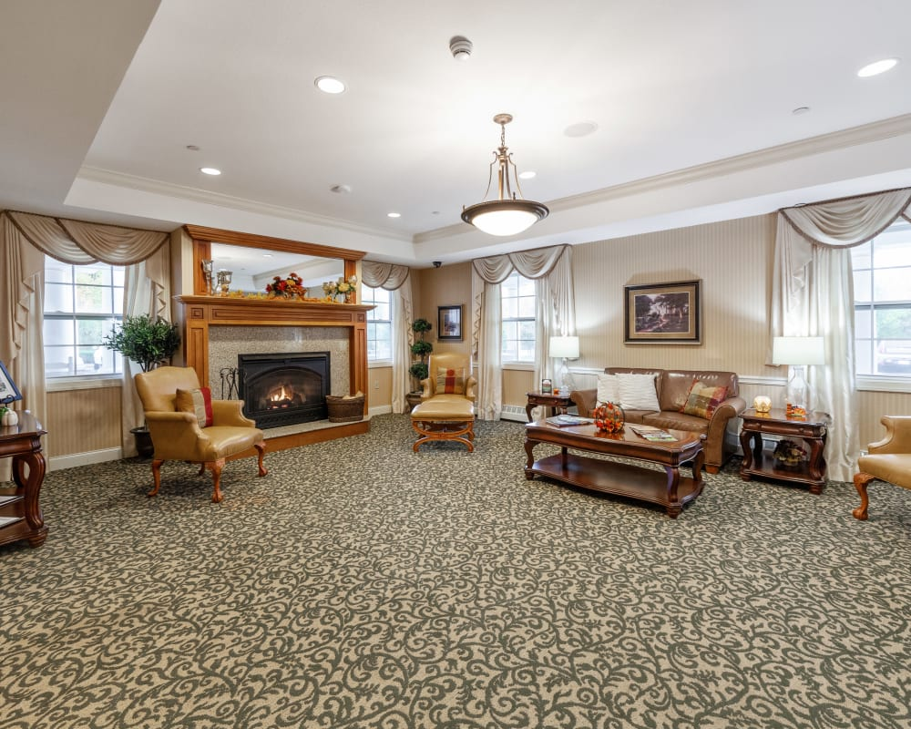 Large carpeted lounge with a fireplace and several places to sit at The Hearth at Tudor Gardens in Zionsville, Indiana