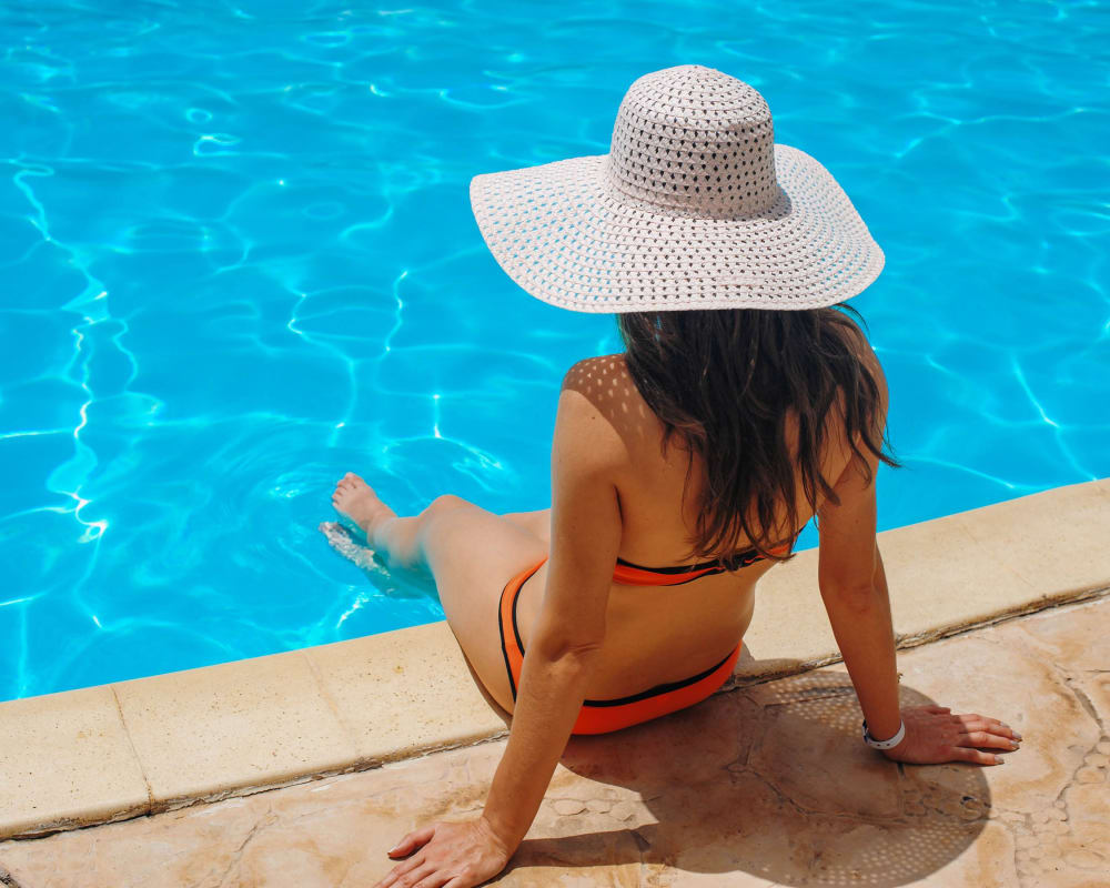 Resident lounging by the pool at St. Charles Square Apartments in Carol Stream, Illinois