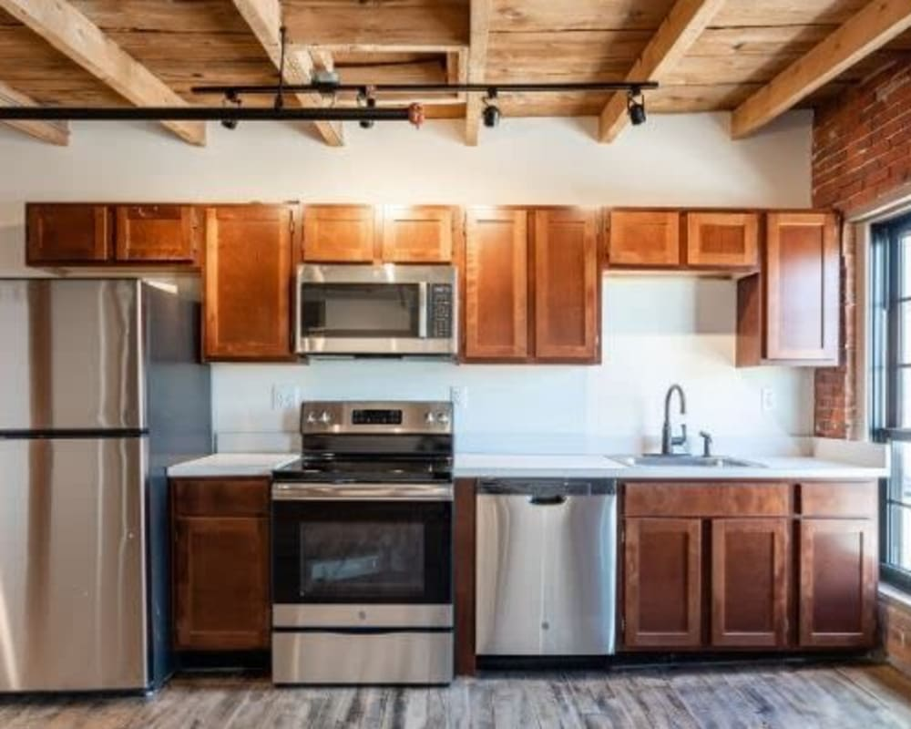 Kitchen with stainless steel appliance at Lofts at Cargill Falls Mill in Putnam, Connecticut