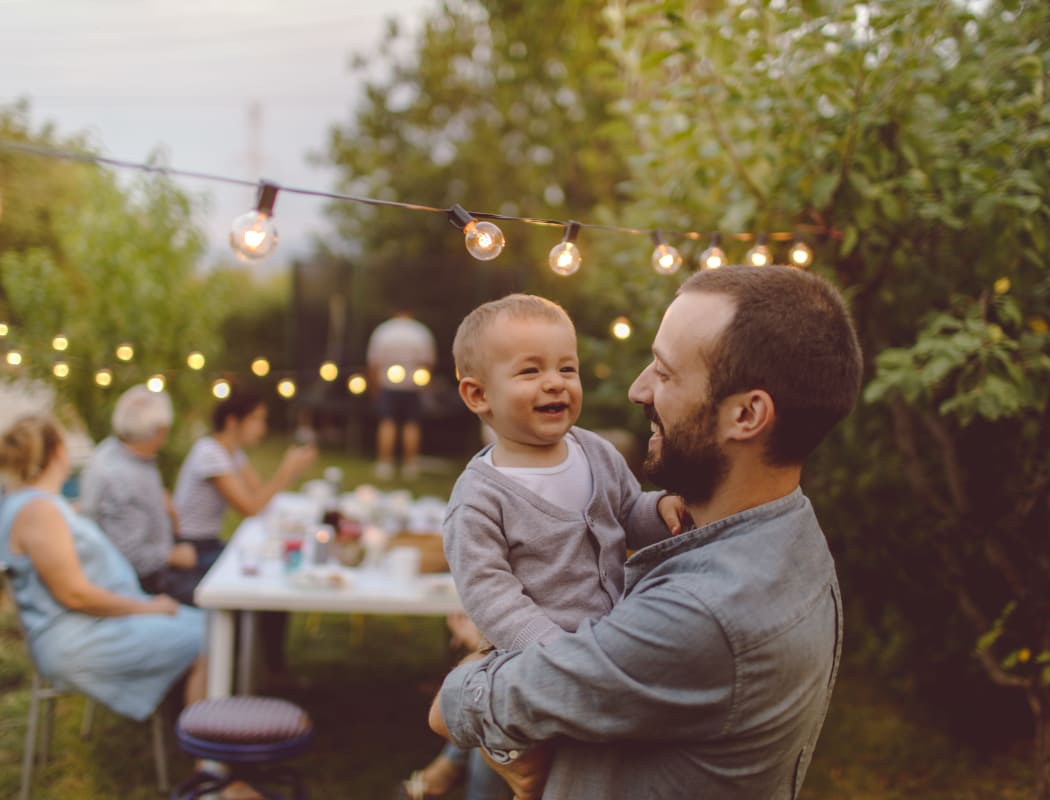 Man holding baby at a company picnic for JMG Realty in Atlanta, GA