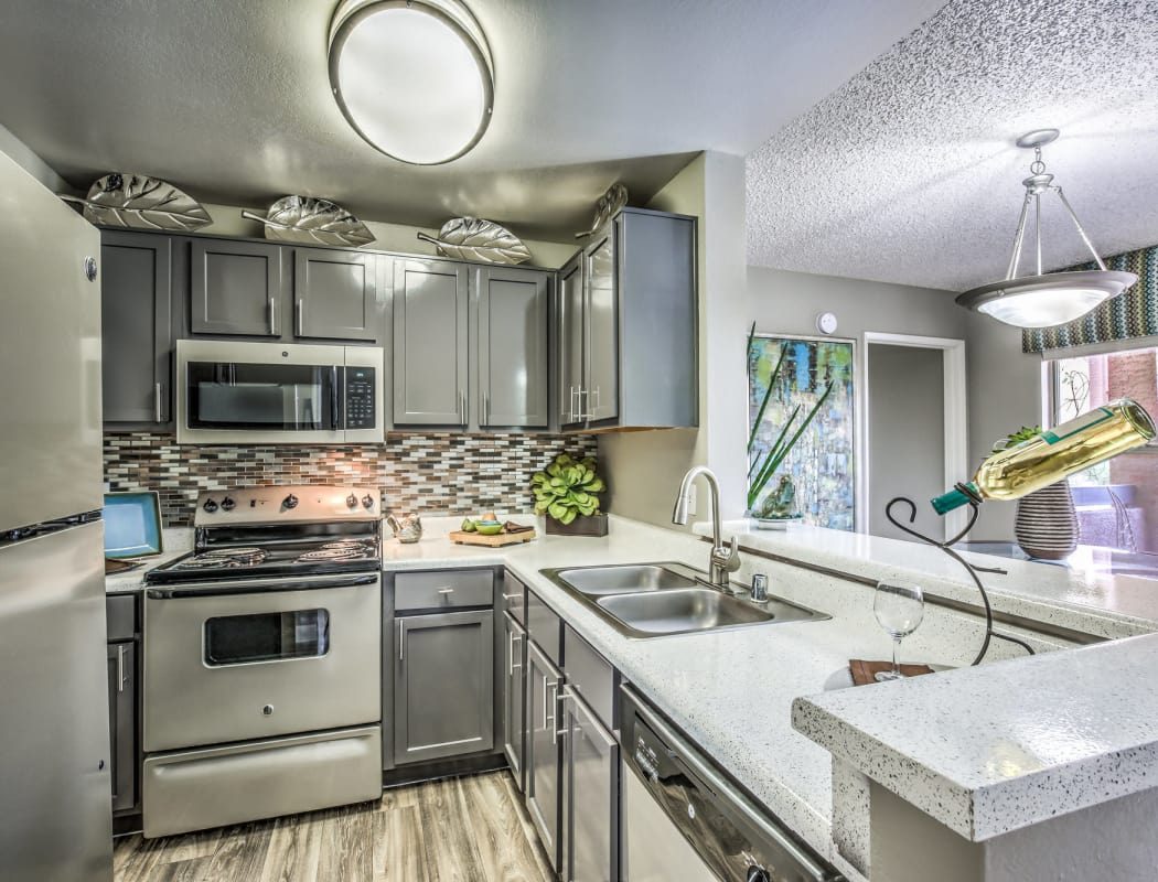 Modern kitchen with granite countertops and stainless-steel appliances in a model home at Solis at Flamingo in Las Vegas, Nevada