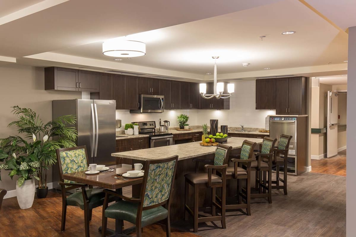 Kitchen with island seating and dining room seating at Avenir Memory Care at Nanaimo in Nanaimo, British Columbia.