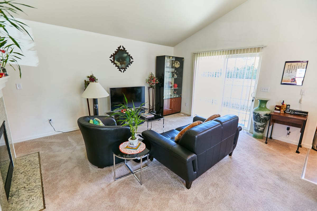 Senior apartment living room with a tv, couch, and chair at South Pointe in Everett, Washington