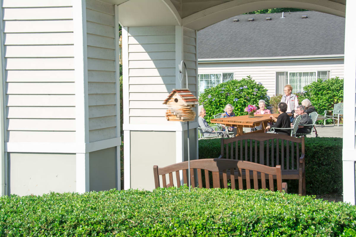 Group of residents sitting outside on the porch at South Pointe in Everett, Washington