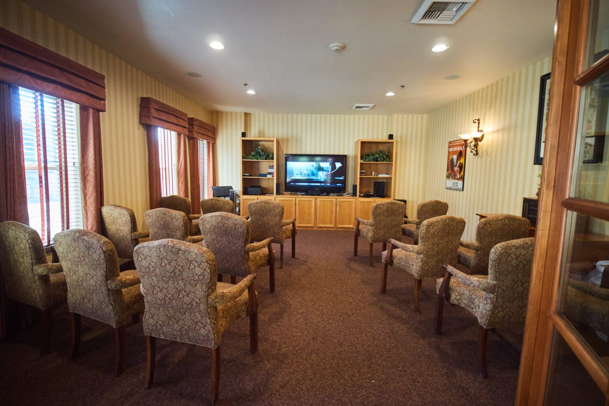 Tv room with rows of chairs for residents at Pioneer Village in Jacksonville, Oregon