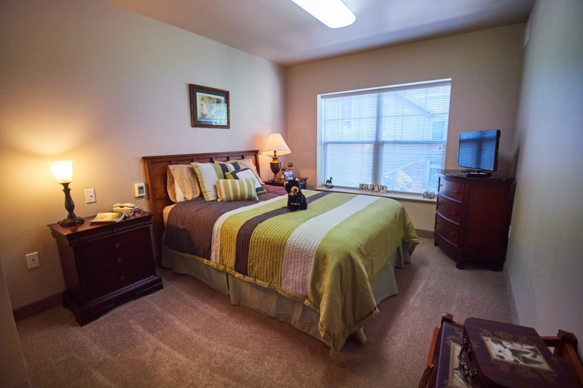 Bedroom with a tv and large windows at Pioneer Village in Jacksonville, Oregon