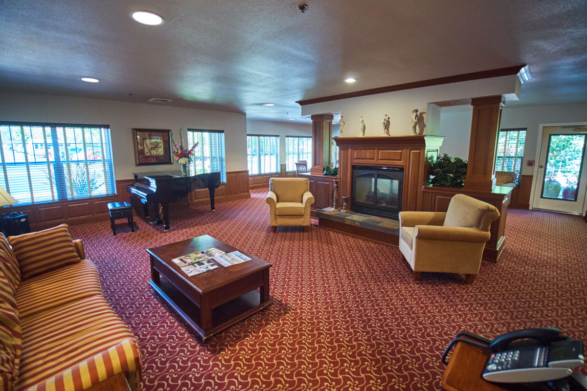 Lounge with a central fireplace and a piano at Pioneer Village in Jacksonville, Oregon