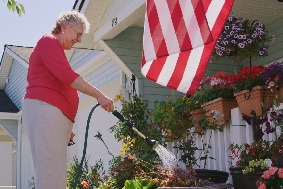 Resident watering the flowers on the porch at Ashley Pointe in Lake Stevens, Washington