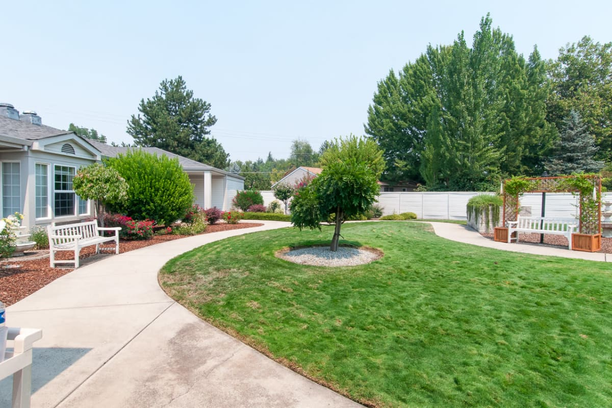 Community courtyard with a paved walkway, benches, and a fountain at Farmington Square Medford in Medford, Oregon