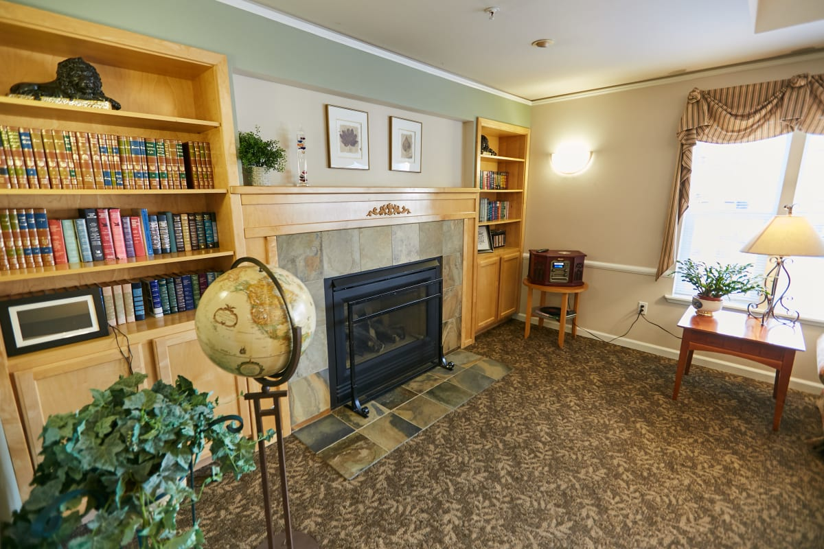 Senior home with a fireplace, bookshelves, and art decorating the living room at La Conner Retirement Inn in La Conner, Washington