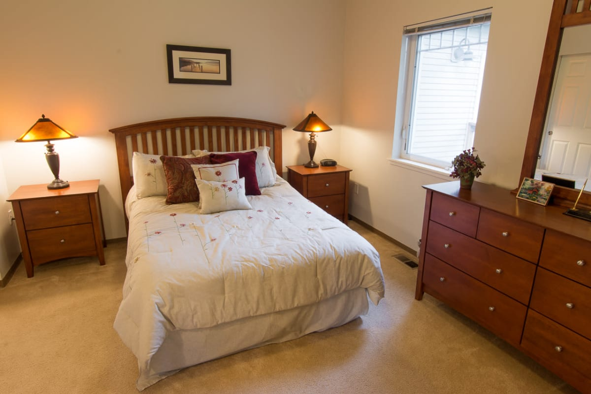 Bedroom with a large bed and window looking out onto the campus at La Conner Retirement Inn in La Conner, Washington