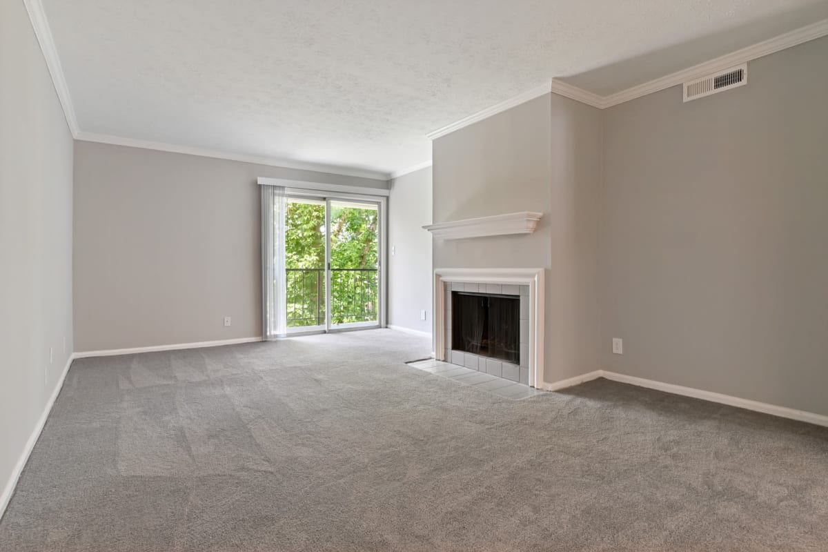 New plush carpeting and a fireplace in the newly remodeled living area of a model apartment at Crest at Riverside in Roswell, Georgia