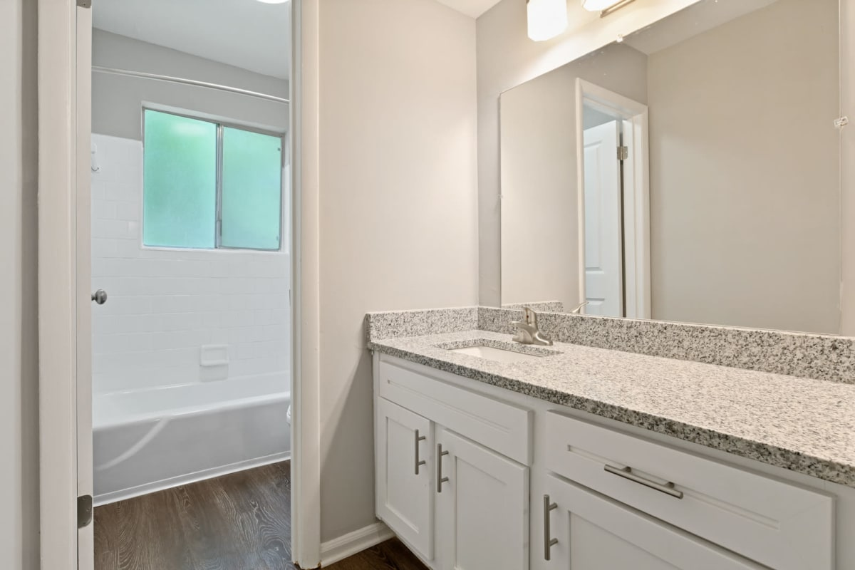 Model apartment's renovated bathroom with a tiled shower and large vanity mirror at Crest at Riverside in Roswell, Georgia