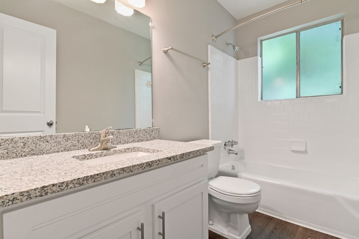 Primary bedroom's renovated en suite bathroom with a quartz countertop and hardwood flooring in a model home at Crest at Riverside in Roswell, Georgia