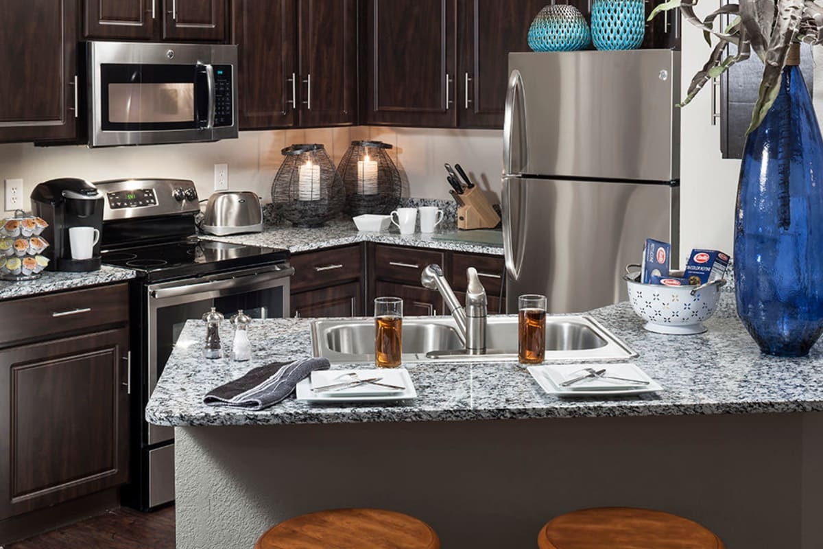 Modern kitchen with stainless-steel appliances and granite countertops in a model apartment at Hyde Park at Montfort in Dallas, Texas