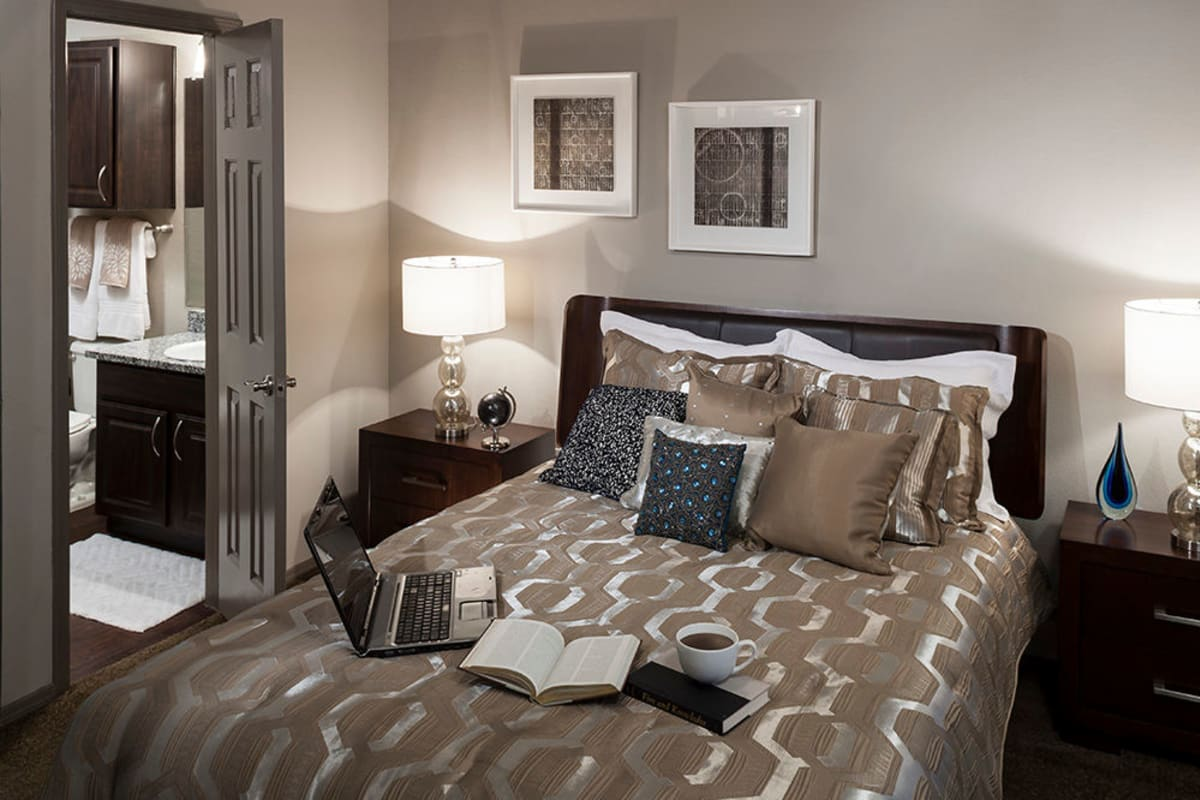 Well-furnished model home's primary bedroom with an en suite bathroom at Hyde Park at Montfort in Dallas, Texas