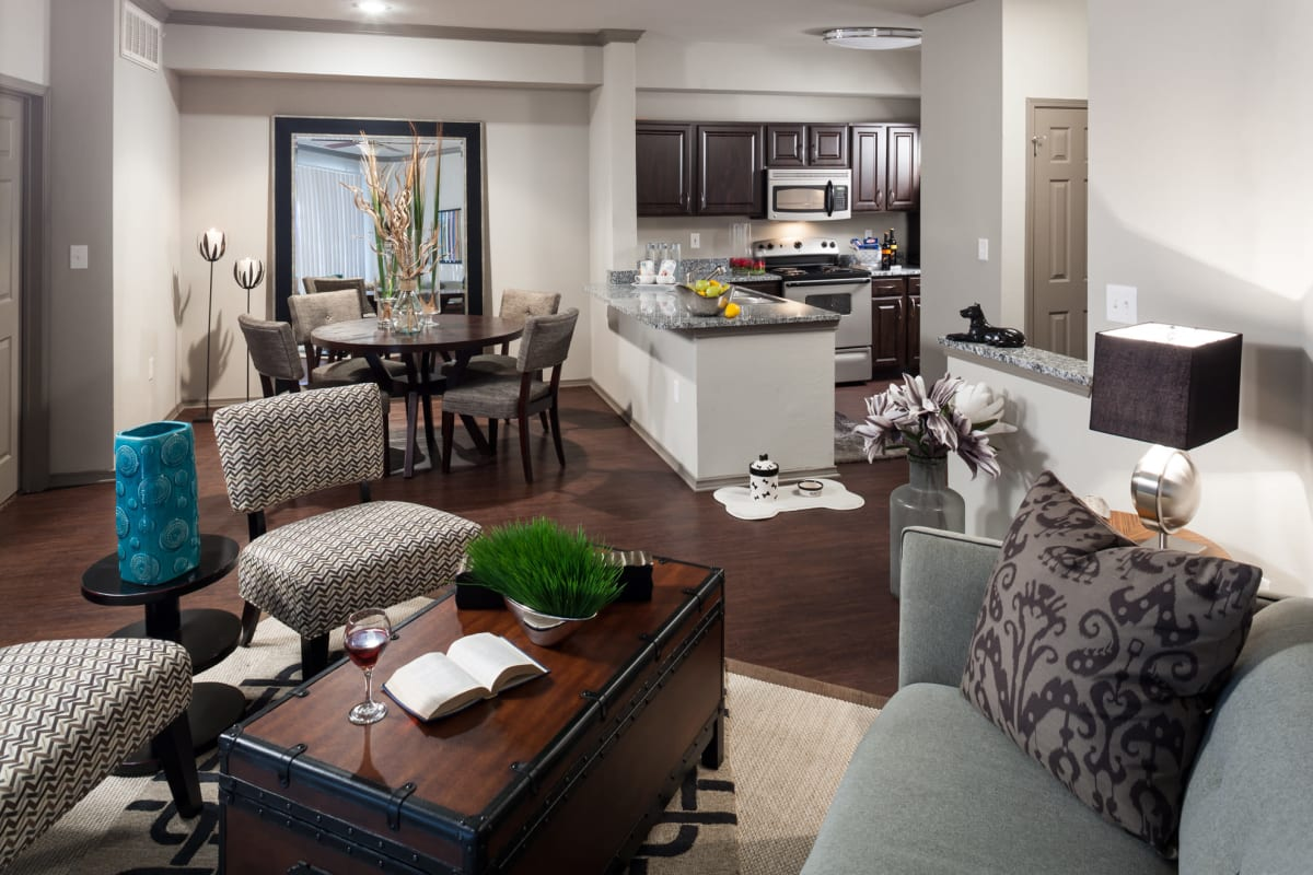 Well-furnished living space with modern decor in a model home's open-concept floor plan at Hyde Park at Montfort in Dallas, Texas