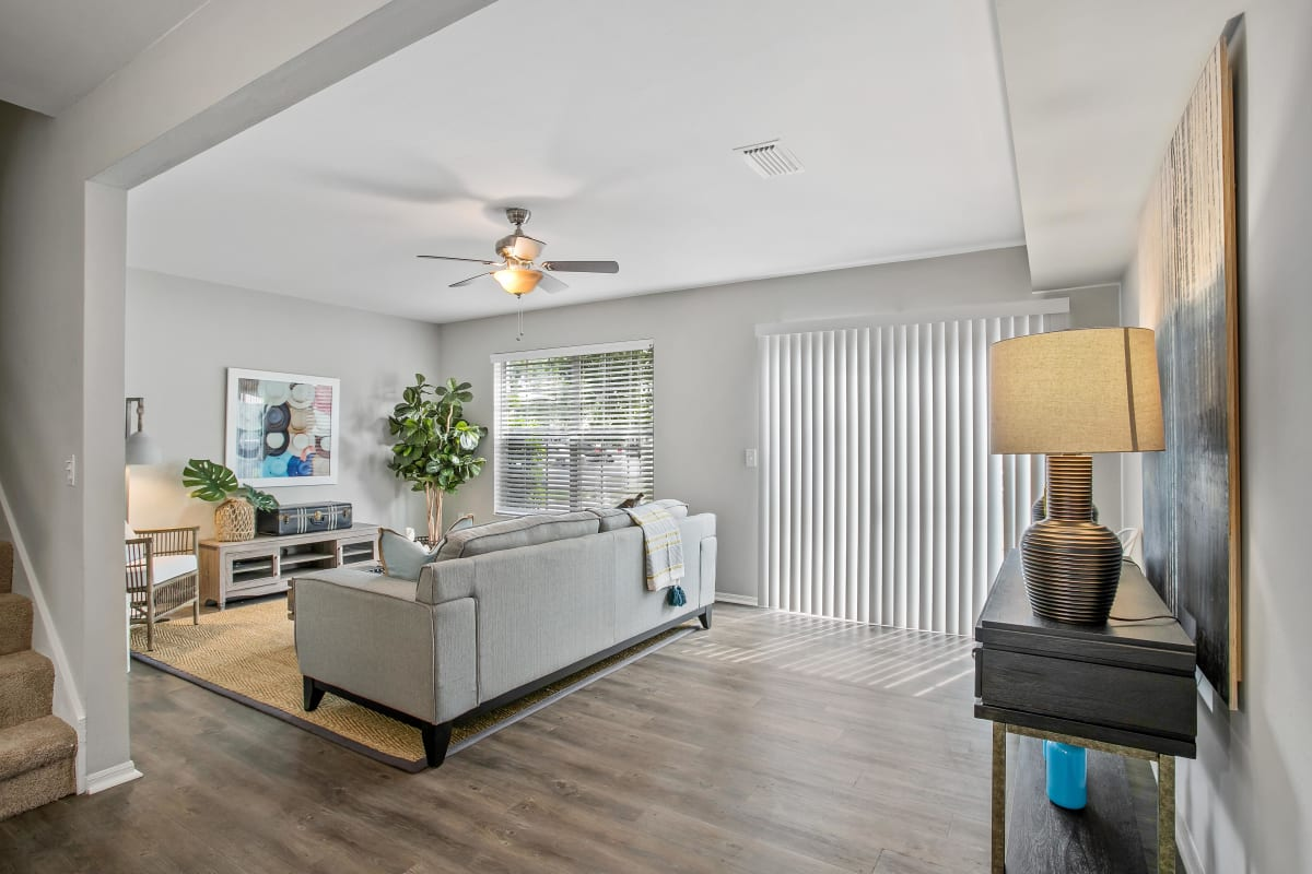 Spacious open-concept townhome's living space with a ceiling fan and hardwood floors at The Coast of Naples Florida in Naples, Florida