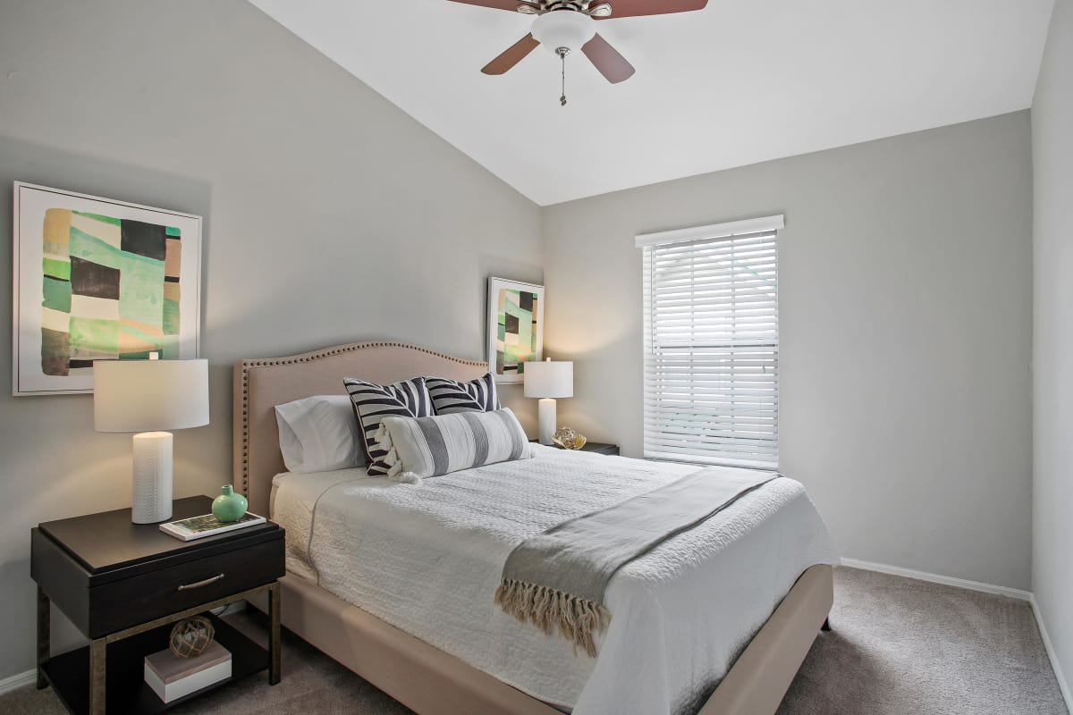 Well-furnished bedroom with a ceiling fan in a model home at The Coast of Naples Florida in Naples, Florida