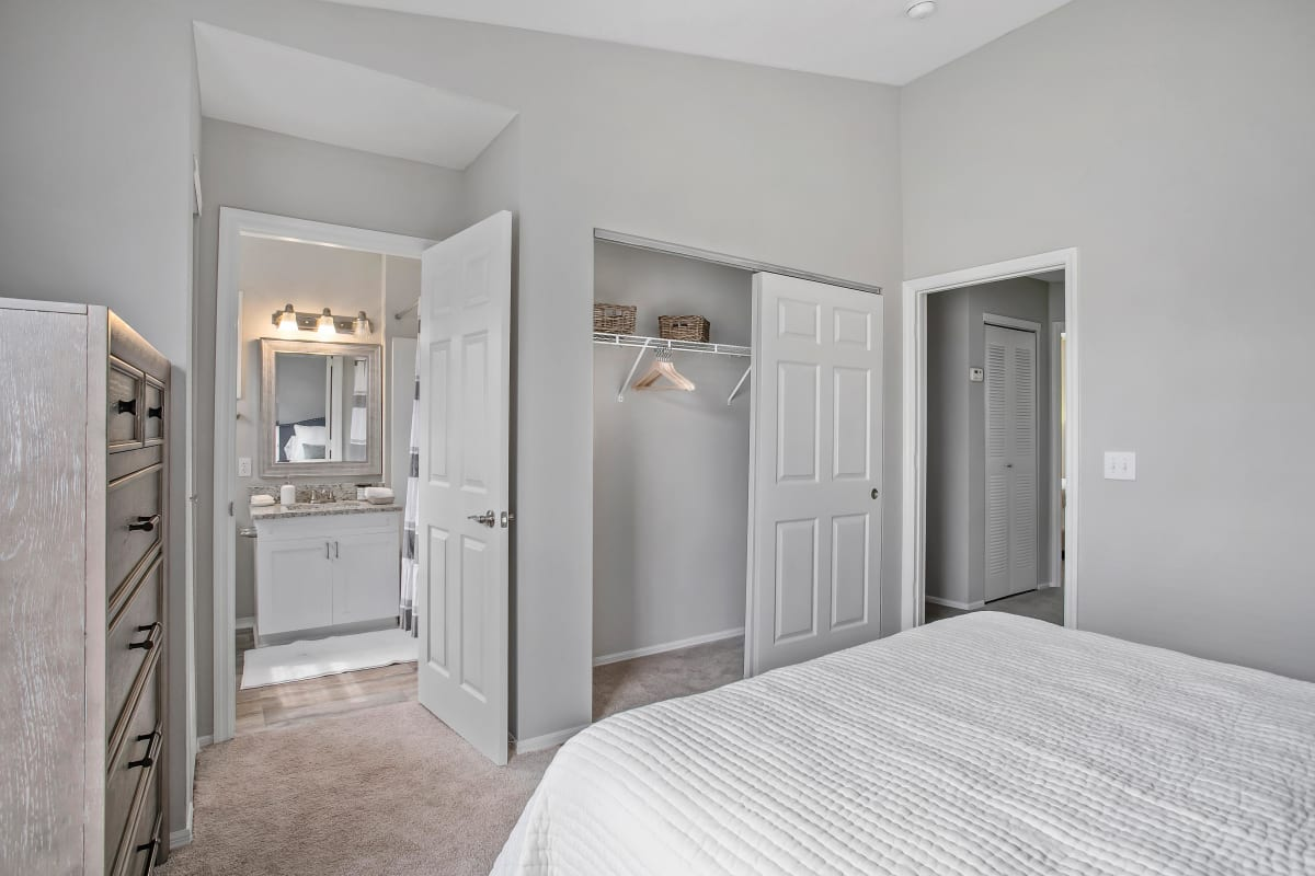 Primary suite with an en suite bathroom and a large closet in a model home at The Coast of Naples Florida in Naples, Florida