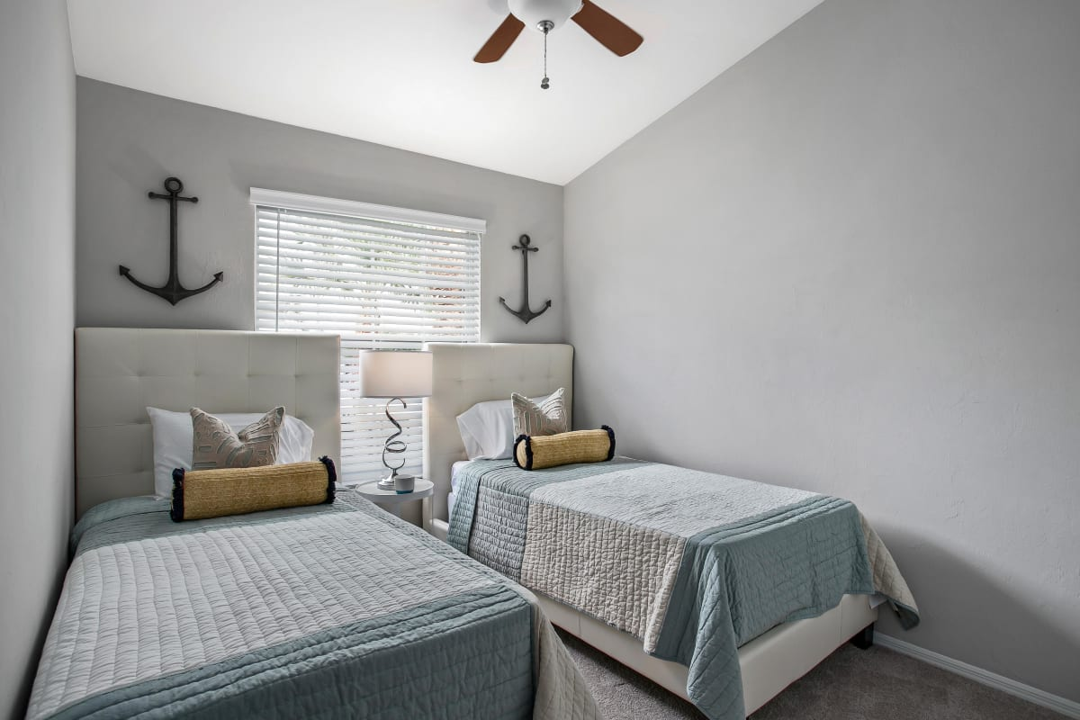 Guest bedroom with two twin beds and a ceiling fan in a model home at The Coast of Naples Florida in Naples, Florida