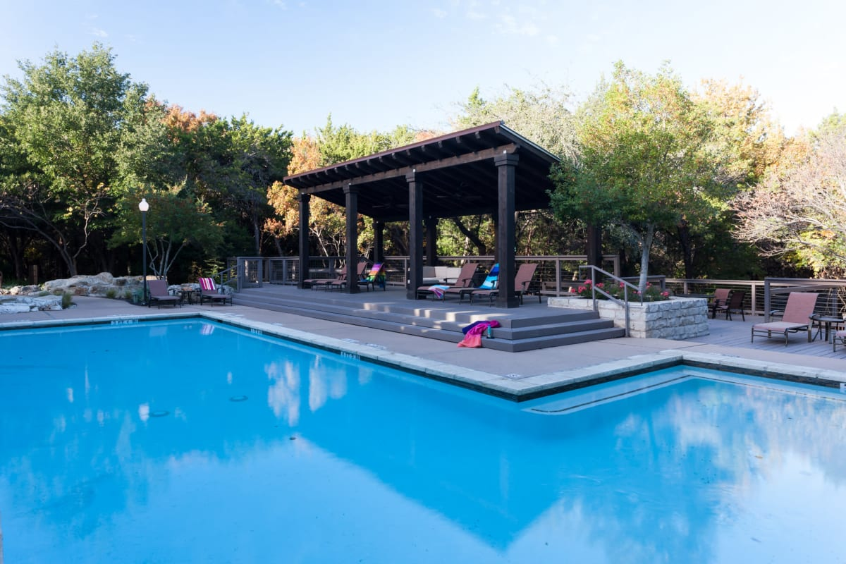 Resort-style swimming pool with shaded areas to relax nearby at Tintara at Canyon Creek in Austin, Texas