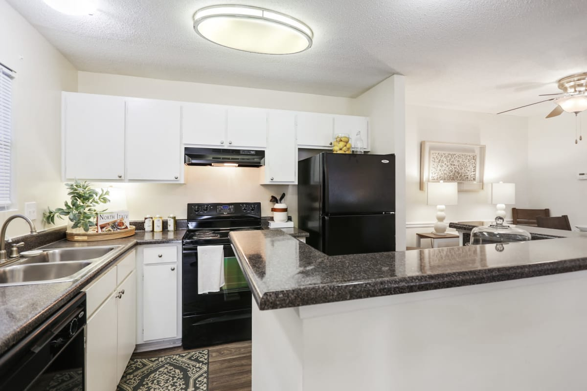 Kitchen with a breakfast bar and bright white cabinetry in a model apartment at Reserve at Peachtree Corners in Norcross, Georgia