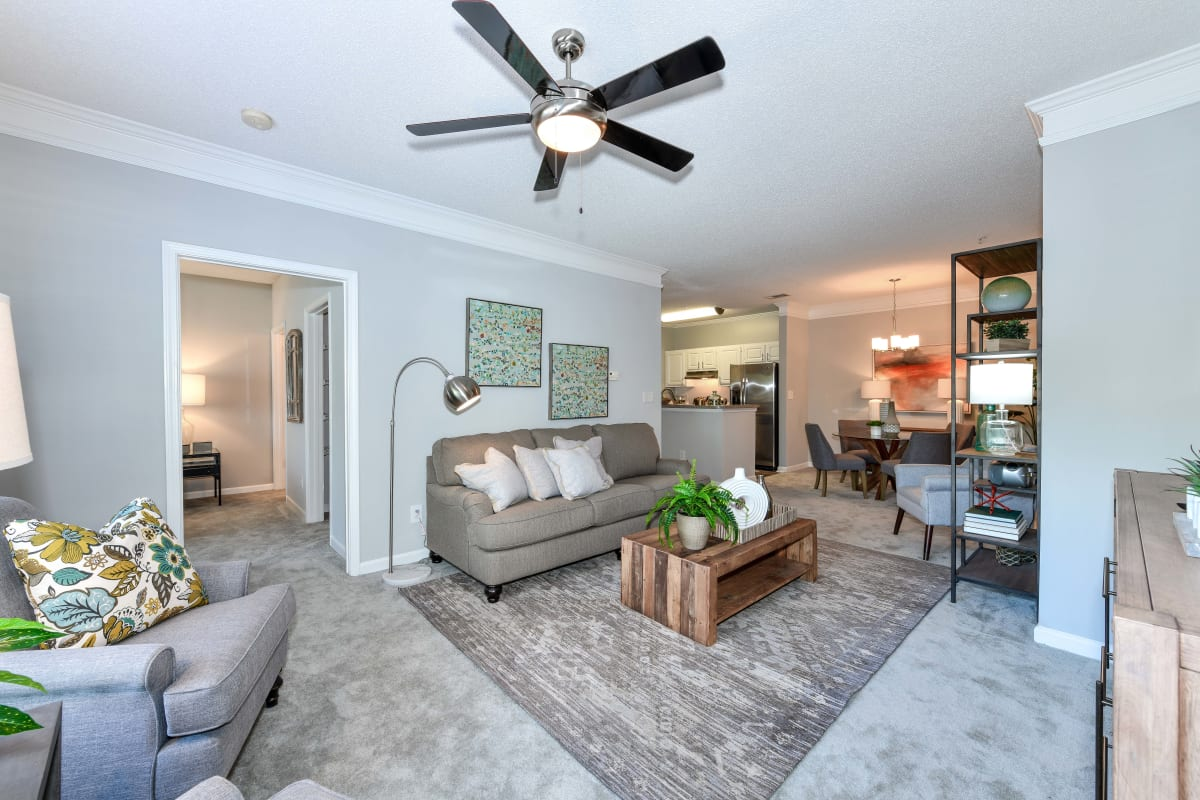 Classically furnished living space with a ceiling fan in a model apartment at 860 South in Stockbridge, Georgia