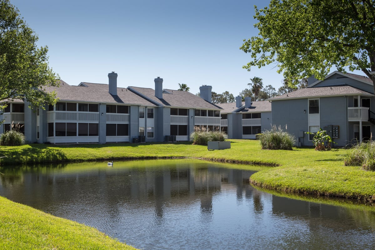 Beautiful green grass and resident buildings around the lake at The Coast at Ponte Vedra Lakes in Ponte Vedra Beach, Florida