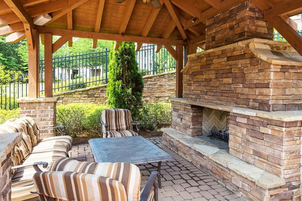 Covered outdoor lounge area with a fireplace at The Preserve at Greison Trail in Newnan, Georgia