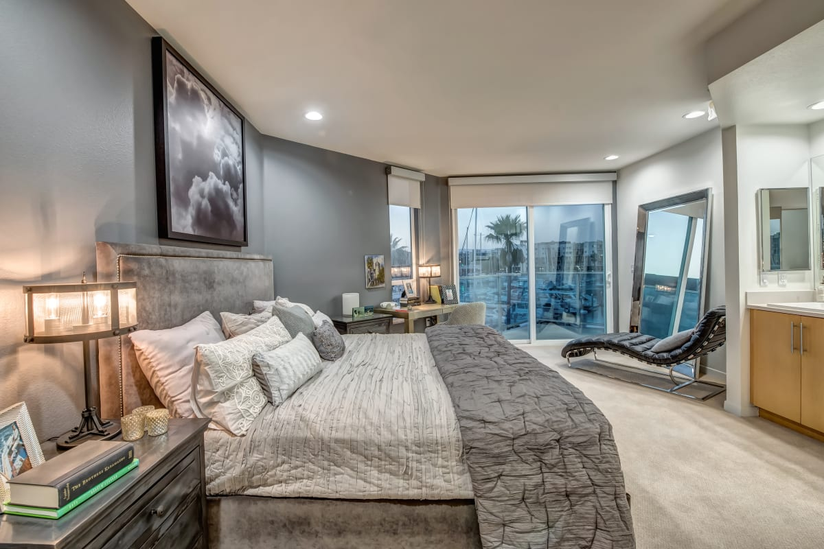 Large primary bedroom with plush carpeting and floor-to-ceiling windows in a model home at Esprit Marina del Rey in Marina Del Rey, California