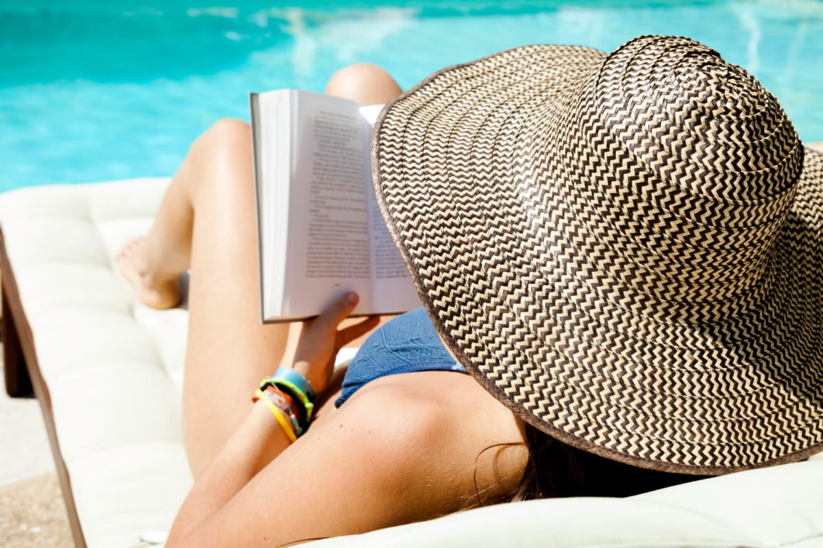 Resident reading by the pool at Courtney Isles in Yulee, Florida