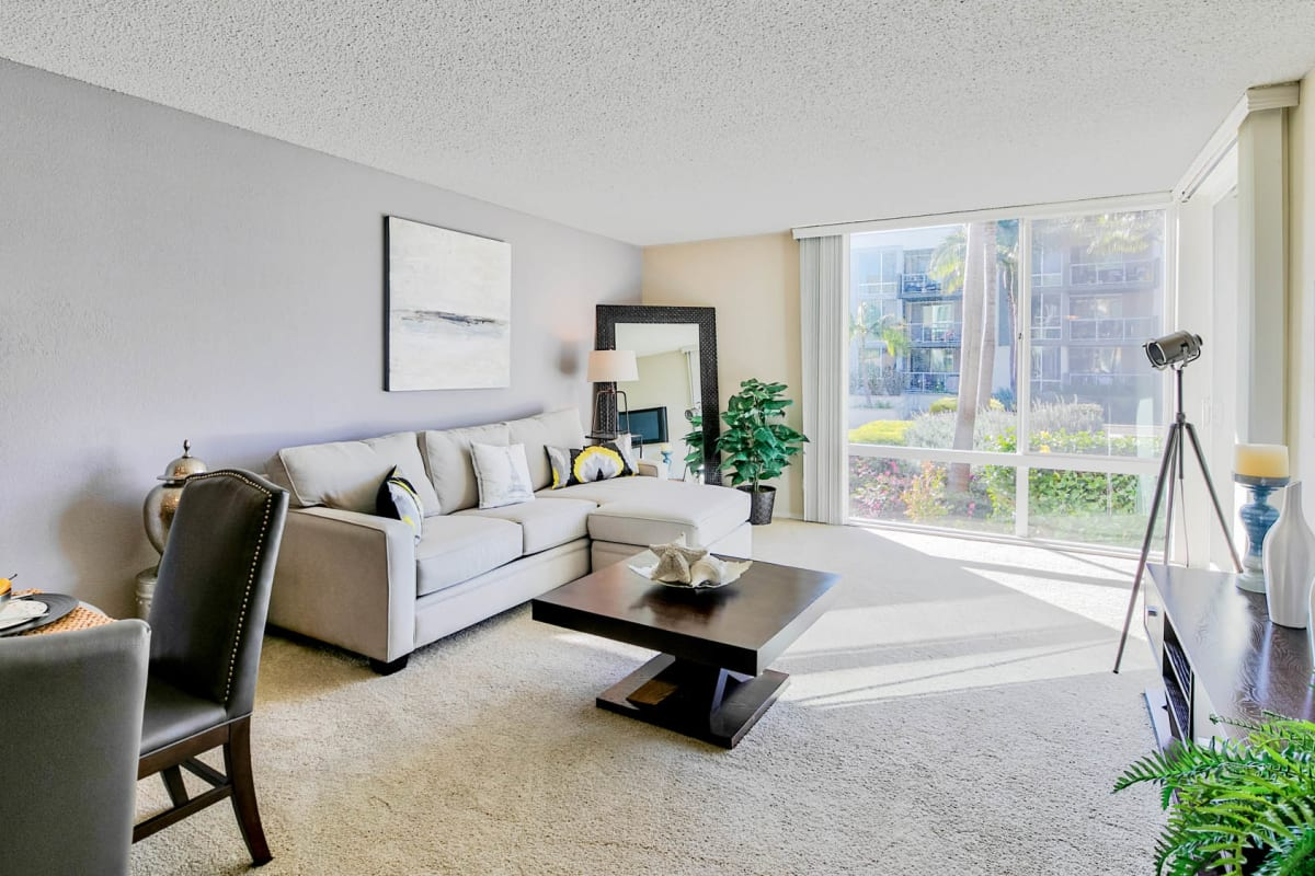 Ample natural light filling the well-furnished livings space of a model apartment at Waters Edge at Marina Harbor in Marina Del Rey, California
