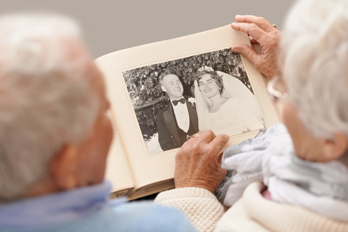 A resident couple looking through an old photo album at Oxford Glen Memory Care at Grand Prairie in Grand Prairie, Texas