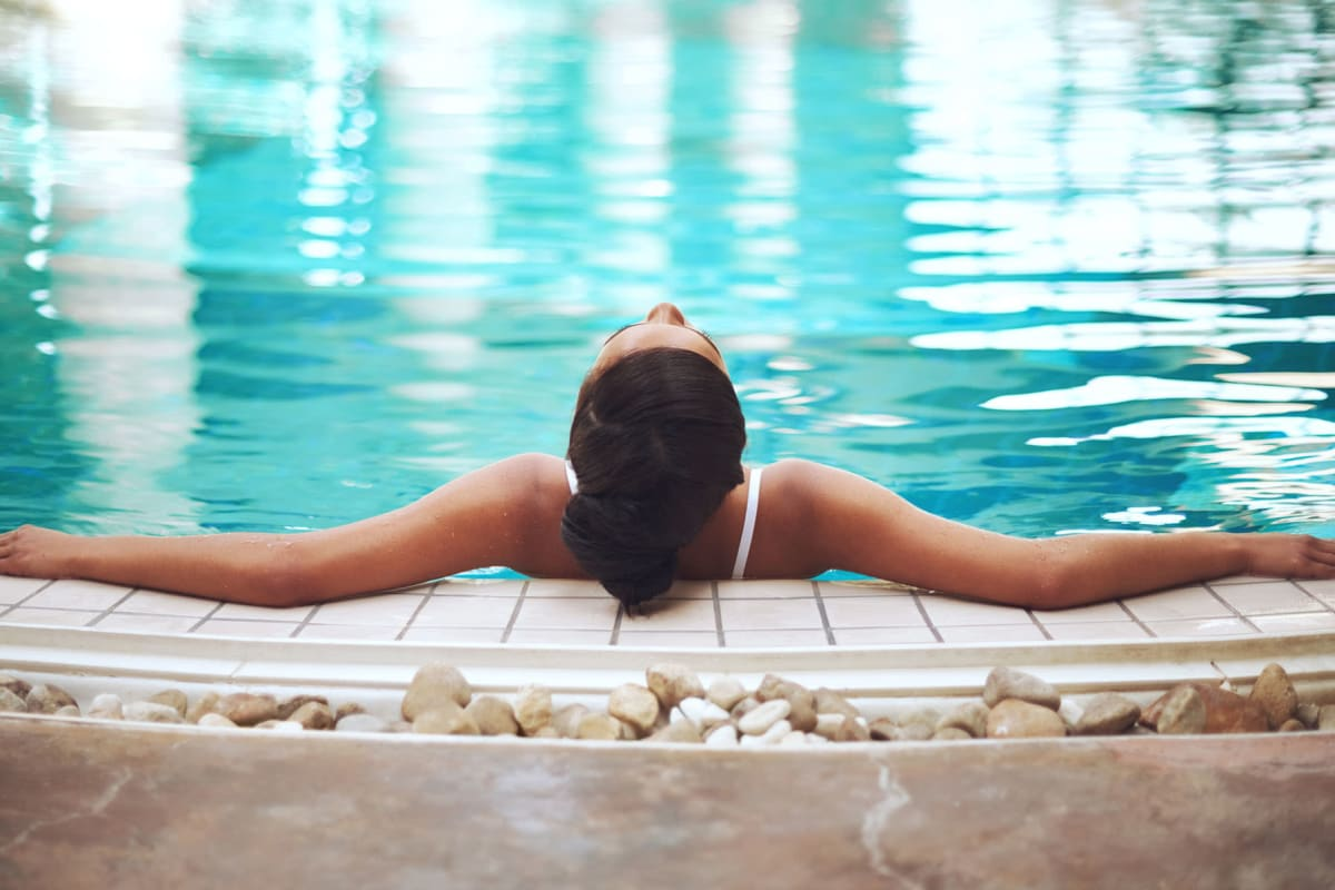 Resident resting her arms on the edge while relaxing in the swimming pool at Solera at City Centre in Palm Beach Gardens, Florida