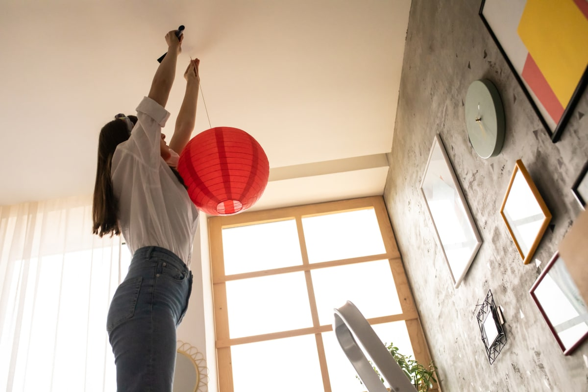 Resident hanging some decor from the high ceiling in her home at Solera at City Centre in Palm Beach Gardens, Florida