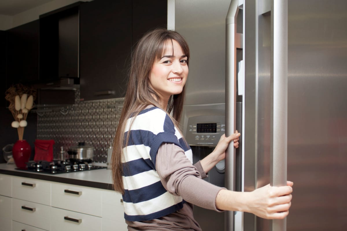 Resident loving the stainless-steel appliances in her new home's kitchen at Solera at City Centre in Palm Beach Gardens, Florida