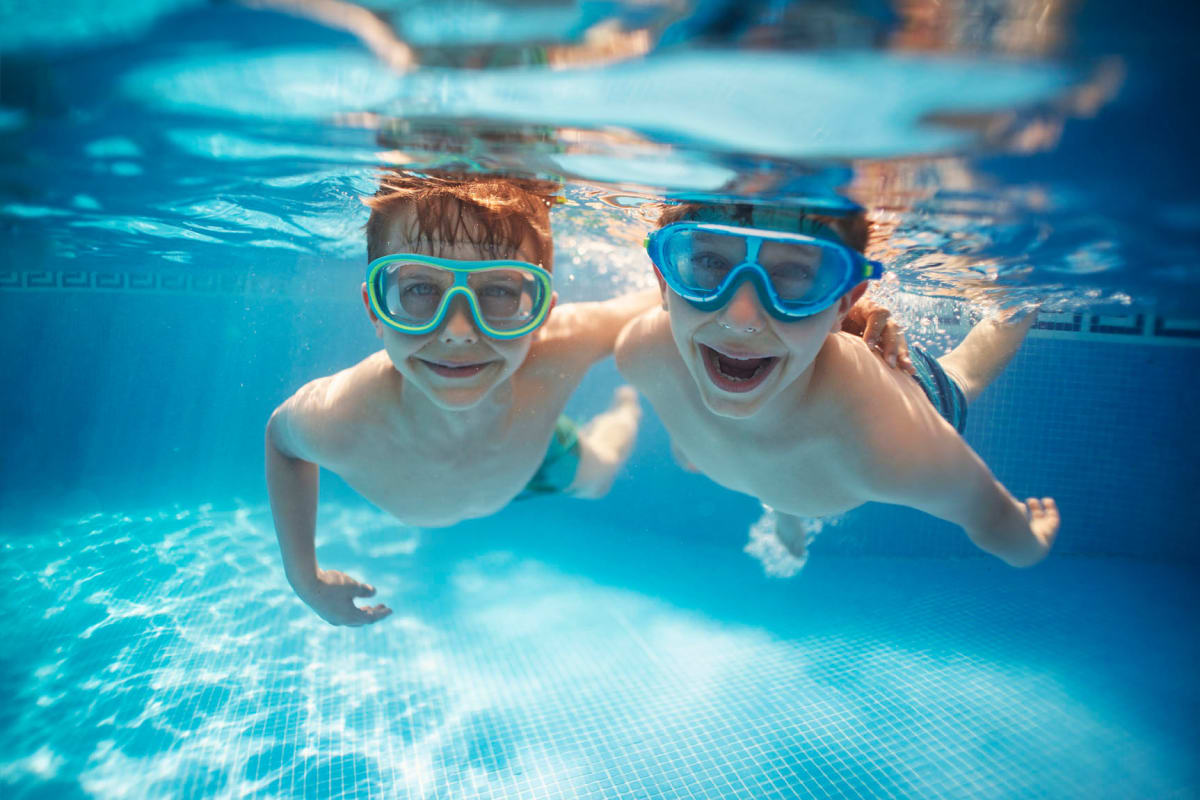 Resident children with goggles on swimming in the pool at Solera at City Centre in Palm Beach Gardens, Florida