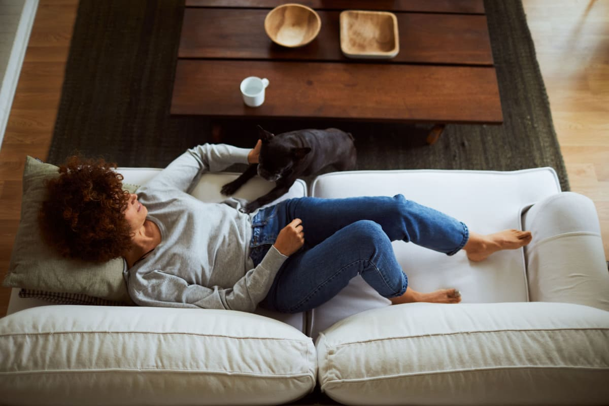 Resident and her pup relaxing on the couch in their apartment after a long day at Valley Plaza Villages in Pleasanton, California