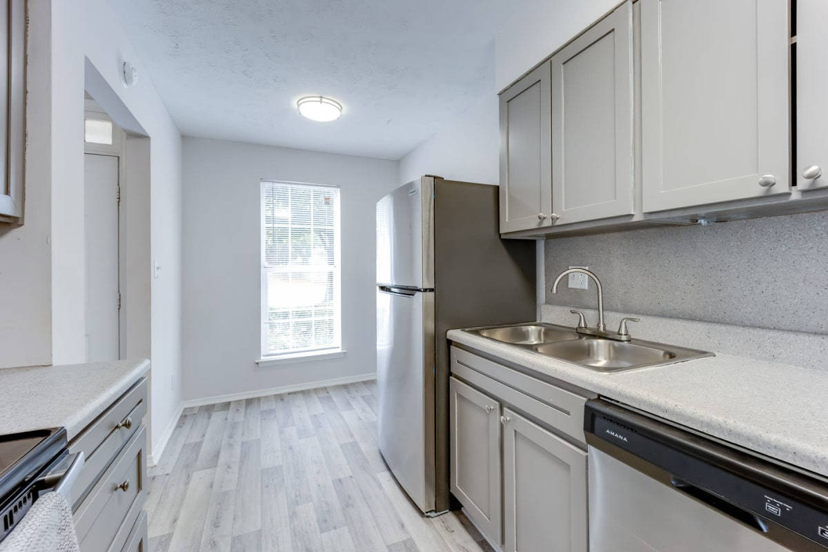 Light grey cabinetry and stainless-steel appliances in an apartment home's kitchen at Sedgefield in Marietta, Georgia