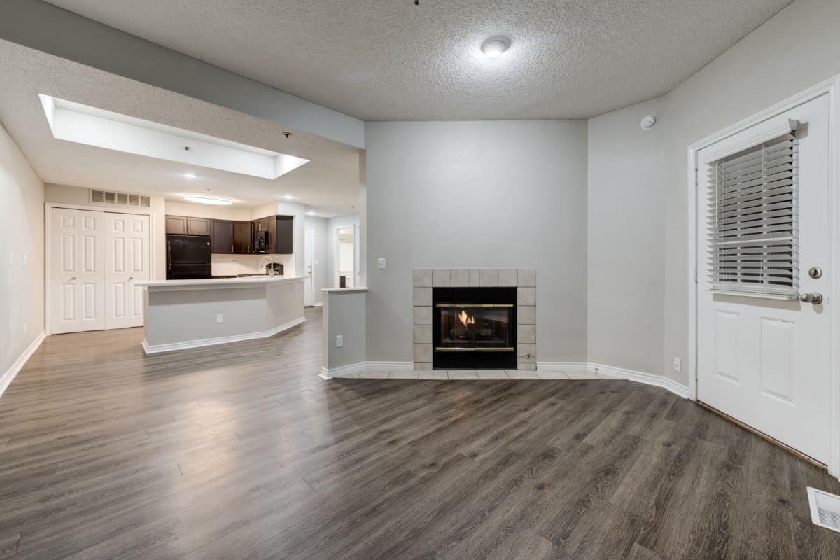 Bright living area with multiple windows and wood flooring at Ashford Belmar in Lakewood, Colorado