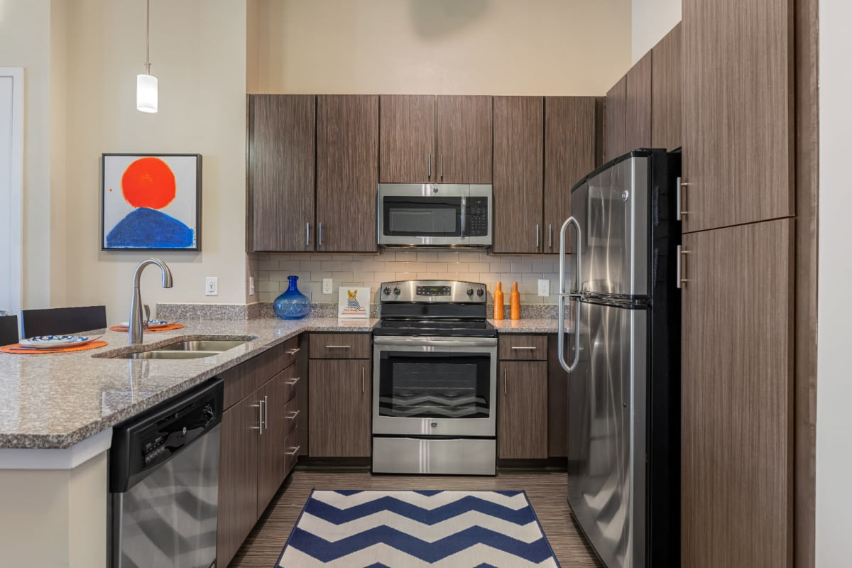 Modern kitchen with stainless steel appliances and granite countertops at Marq at Crabtree in Raleigh, North Carolina