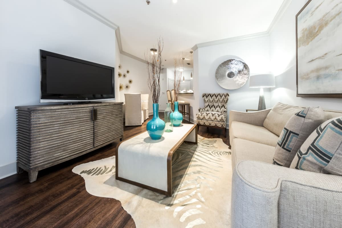 Full size couch, coffee table, entertainment center, and single chair in living room at Marq Eight in Atlanta, Georgia