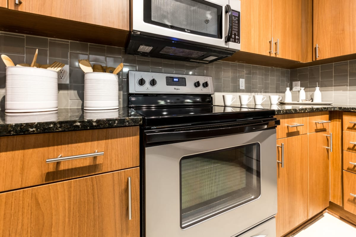 Stainless steel stove/oven and microwave with wood cabinets at Marq Eight in Atlanta, Georgia