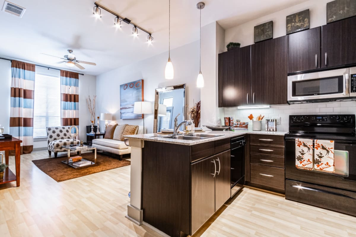 Modern style open plan with stainless steel kitchen appliances and wood flooring at The Marq on Voss in Houston, Texas