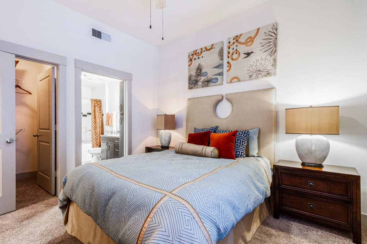 Carpeted bedroom with large bed, private bathroom, and walk-in closet at The Marq on Voss in Houston, Texas